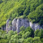 Blick zu den Felsen über der Dreieingangshöhle