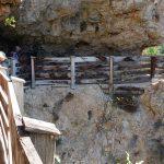 Wandeern zum Wallfahrtsort San Romedio am steilen Felshang. Der Weg diente einst ähnlich einer Levada zur Wasserversorgung.